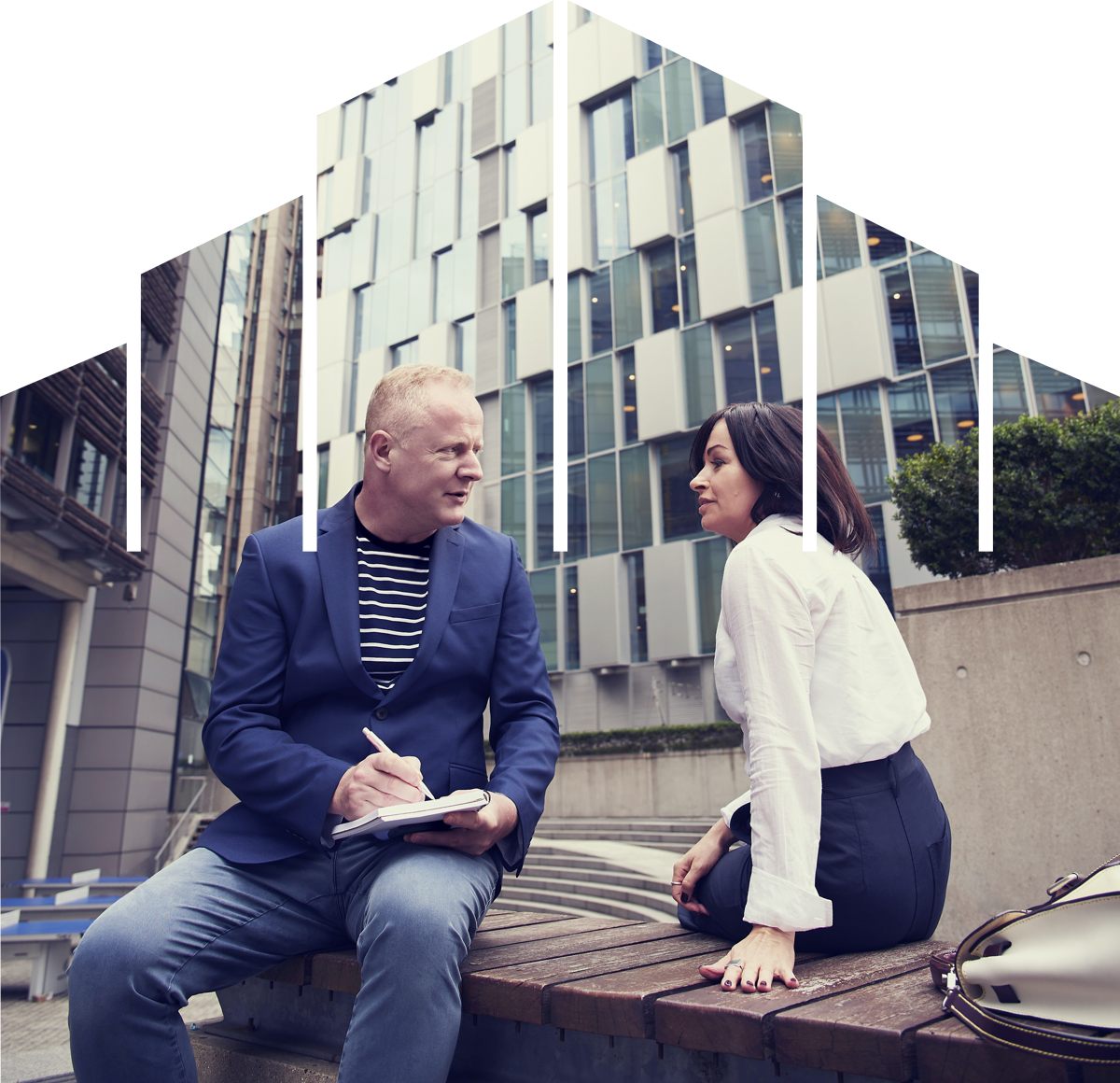 man-and-woman-sitting-on-wooden-bench-outside-buildings